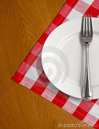 White plate and fork on wooden table w tablecloth