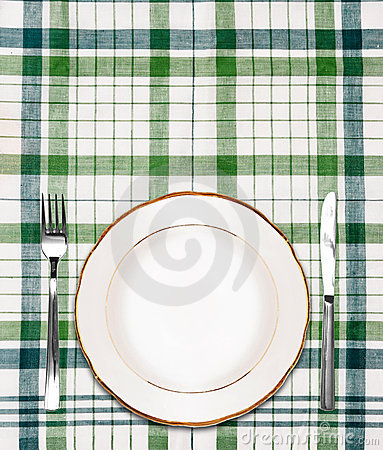 White plate on green checkered tablecloth