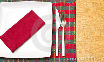 White plate on green and red tablecloth