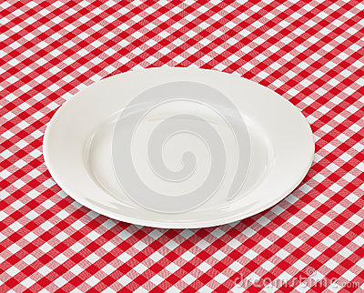 White plate over red picnic tablecloth