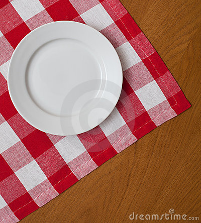 White plate on wooden table with red tablecloth