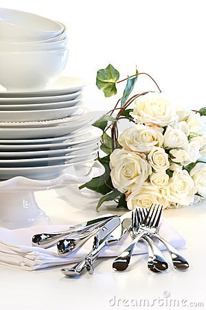 White plates stacked with utensils and roses