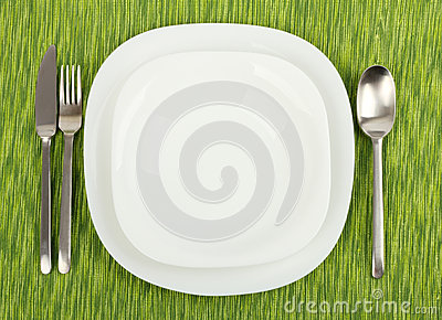 Plates with utensils on a green tablecloth.