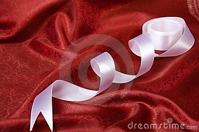 White ribbon on red drape