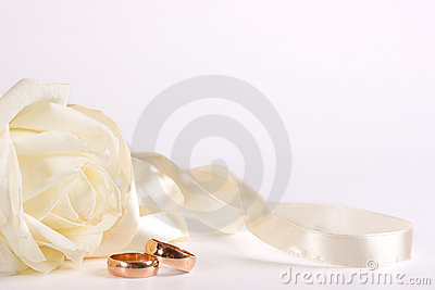 White rose, wedding ring and ribbon