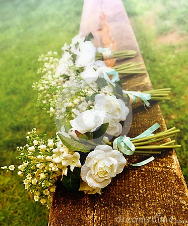 White roses on a bench before a country wedding