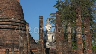 White sculpture of Buddha on the ruins of an Buddhist temple. Sukhothai. White sculpture of sitting Buddha on the ruins of an ancient Buddhist temple Wat Sa Si stock video footage