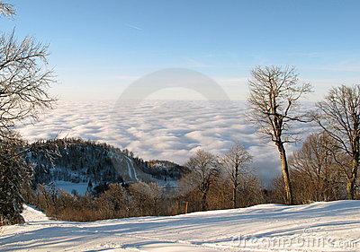 White ski slope above puffy clouds