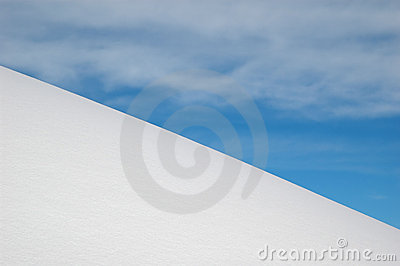 White snow slope, blue sky and white clouds