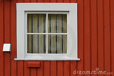 White square window set in a red wooden wall