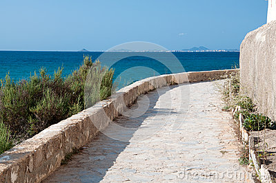 White stone pavement path along rocky seashore.