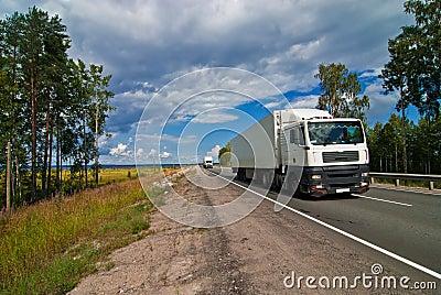 White trucks traveling on the highway