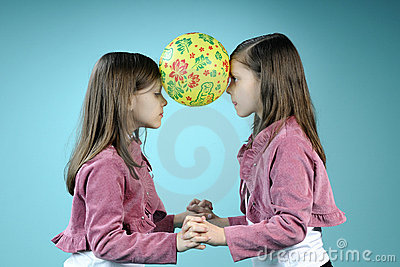 White twin sisters having fun with ball
