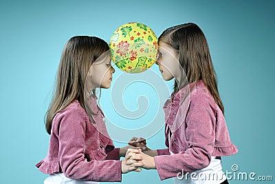White twin sisters having fun with ball