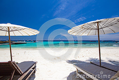 White umbrella and chairs on white beach
