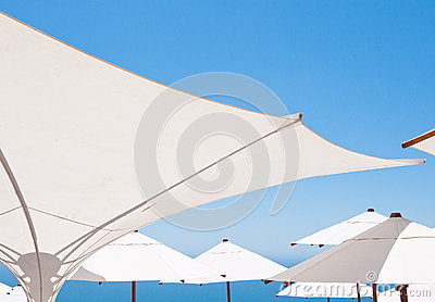 White umbrellas with blue sky in background