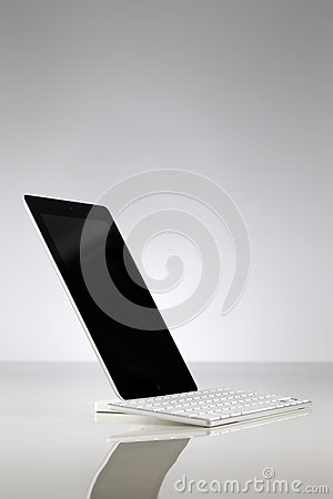 A white usb keyboard attached to a tablet Editorial Image
