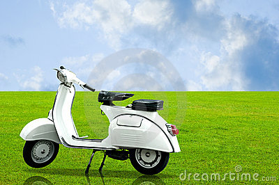 White vintage motobike parking on the grass