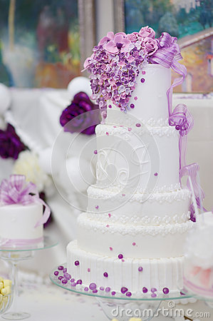 White wedding cake decorated with purple flowers