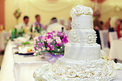 White wedding cake on interior background