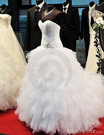 White wedding dress with black suits in background
