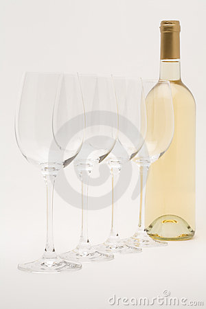 White wine bottle with wineglasses lined up