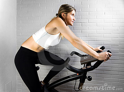 White Woman rides Exercise Bike