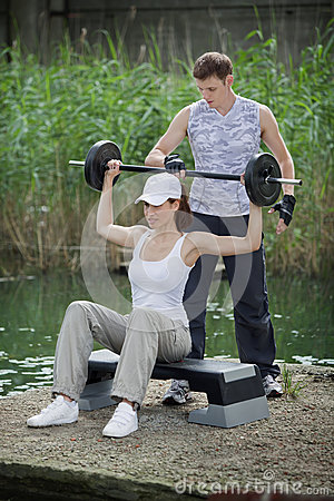 Woman exercising with personal trainer with barbell - outdoor