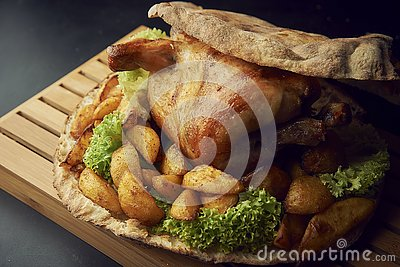 Whole baked chicken with potatoes close-up on a table Stock Photo