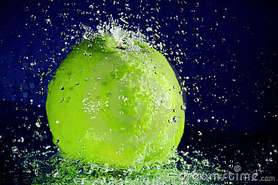 Whole green apple with stopped motion water drops