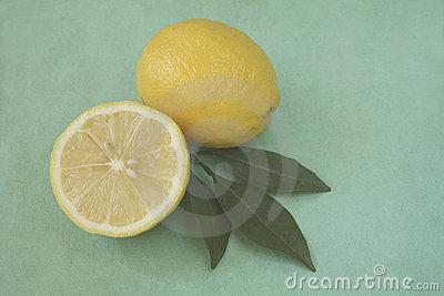 Whole and half lemon with leaves