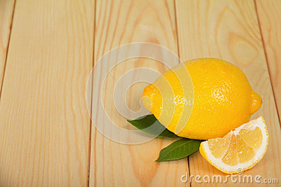 Whole and half lemon on wooden table