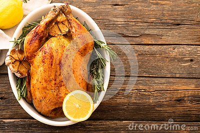 Whole roasted chicken with lemon and rosemary on a black plate. Rustic style. Christmas concept. Christmas turkey. Stock Photo