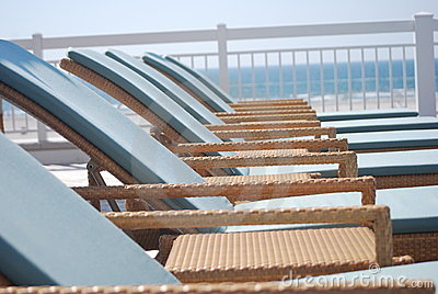 Wicker lounge chairs poolside by the beach