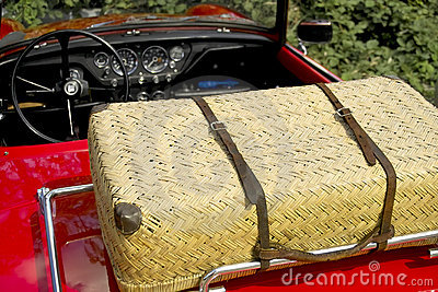 Wicker picnic basket on a red sports car