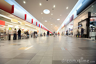 Wide hall and buyers in trading centre with shops