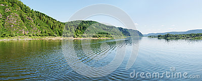 Wide panorama of a river and the forested mountain