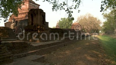 Ancient ruins in Sukhothai Historical Park. A wide shot of an ancient ruin in Sukhothai Historical Park, Thailand, showing a large, seated Buddha image stock video footage