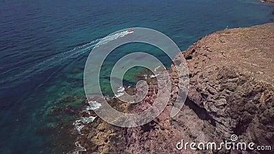 Widok z lotu ptaka strzępiaste plaże Lanzarote i brzeg, Hiszpania, kanarek Czerwony dinghy żegluje z pełną prędkością zdjęcie wideo