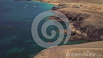 Widok z lotu ptaka strzępiaste plaże Lanzarote i brzeg, Hiszpania, kanarek Czerwony dinghy cumujący w zatoczce Papagayo zdjęcie wideo