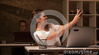 Wielka caucasian kobieta bierze selfies na jej smartphone podczas gdy siedzący w biurze z jej kolegą, oddzieleni biurka zdjęcie wideo