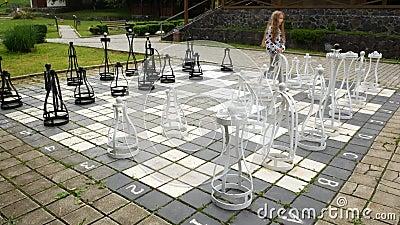 Wielki chessboard w jardzie Dziecko przemienia ciężkich szachowych kawałki zbiory wideo