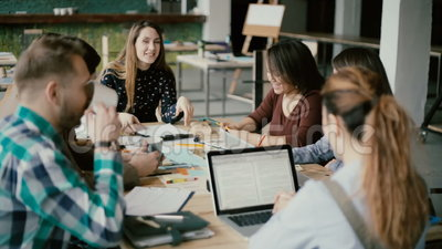 Wieloetniczna grupa ludzi w nowożytnym biurze Kreatywnie biznes drużyna pracuje na projekcie wpólnie, roześmiana i uśmiechnięta, zbiory