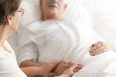 Wife caring about dying spouse Stock Photo