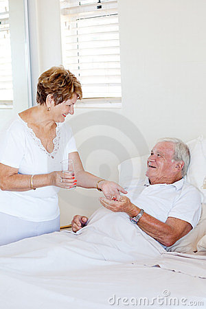 Wife giving medicine to husband