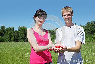 Wife, husband hold berry in hands