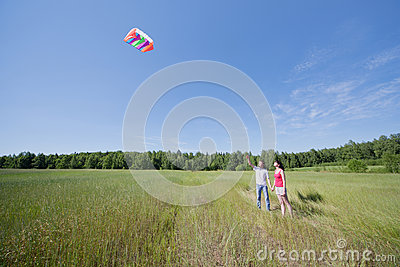 Wife, husband launch kite in field