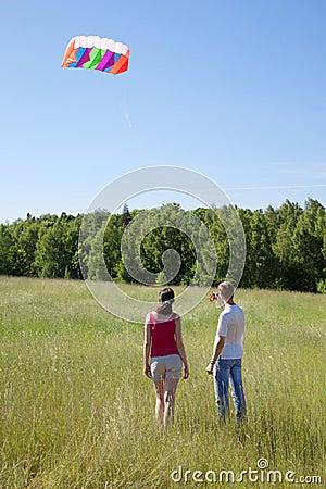 Wife, husband launch kite in field