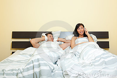 Wife phone in bed with frustrated husband