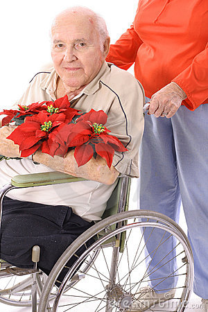 Wife pushing handicap man in wheelchair with flowe